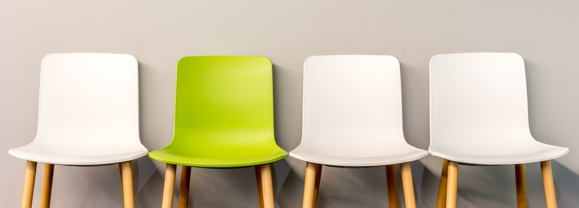 One Green and Three White Aligned Chairs